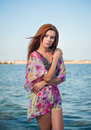 Young sexy red hair girl in multicolored blouse posing on the beach sensual attractive woman with long hair summer shot at sea Stock Photos
