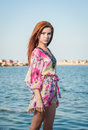 Young sexy red hair girl in multicolored blouse posing on the beach. Sensual attractive woman with long hair, summer shot at sea Royalty Free Stock Photo