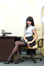 Young sexy woman in black stockings sitting on workplace in  off Royalty Free Stock Photo