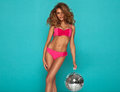 Young sexy woman happy in pink lingerie holding disco ball Royalty Free Stock Image