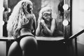 Young sexy woman looking at mirror black and white Royalty Free Stock Images