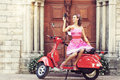 Young and sexy woman with a motor scooter retro style image her vintage photo camera Stock Image