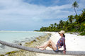 Young sexy woman relaxing on deserted tropical island coconut palm tree a in aitutaki lagoon cook islands Royalty Free Stock Photography