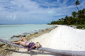 Young sexy woman sunbathing on deserted tropical island coconut palm tree a in aitutaki lagoon cook islands Royalty Free Stock Images