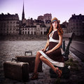 Young sexy woman traveler with two old brown suitcases sitting on a bench in a european city Stock Photos