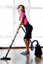 Young sexy woman with vacuum cleaner cute brunette using on floor in her home Stock Image