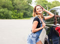 Young sexy woman with wrench in hands and car on background Royalty Free Stock Photo