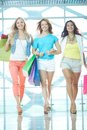 Young shopaholics portrait of three glamorous girlfriends with paperbags walking down trade center Royalty Free Stock Photography