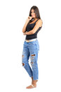 Young shy hispanic beauty in casual clothes looking at camera full body length portrait isolated over white studio background Royalty Free Stock Photo