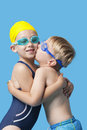 Young siblings in swimwear embracing and kissing over blue background Royalty Free Stock Photos