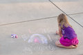 Young sidewalk artist a girl makes a chalk design on a light pavement room at the top for copy text Stock Images
