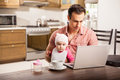 Young single dad working at home with his baby attractive on a laptop computer while taking care of daughter Royalty Free Stock Images
