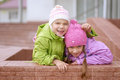 Young sisters laughing and hugging two near beautiful building Stock Photography