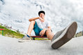 Young skater resting sitting on his skateboard in a skatepark Royalty Free Stock Photo