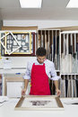 Young skilled worker adjusting frame on photograph Royalty Free Stock Image