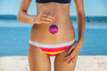 Young, skinny, pretty girl in a striped bathing suit holding a pink Christmas ball in hand, on the ocean, the sea. Royalty Free Stock Photo