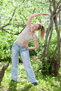 The young slender woman does sporting training in park portrait in a sunny day Royalty Free Stock Images