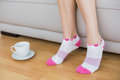 Young slender woman wearing pink socks sitting on couch Royalty Free Stock Photography