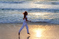 The young slender woman in white clothes in runs in the area of a surf at sunset silhouette running on along ocean coast Royalty Free Stock Photography