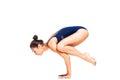 Young slim flexible woman doing arm balance yoga pose