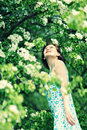 Young slim girl enjoying blooming apple tree. Royalty Free Stock Photo