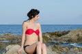Young slim pretty lady wear bikini sitting on sea rocks gaze the ocean red and black Stock Photography