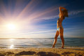 Young slim sexy woman in bikini standing on beach and looking at sunrise on the sea. Royalty Free Stock Photo