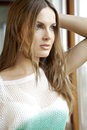 Young slim sexy woman in green white sweater against the window and attractive brunette Royalty Free Stock Photos