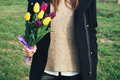 Young slim woman in coat standing on green grass and holding a b Royalty Free Stock Photo