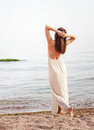 Young slim woman dressed in long white dress with open back, relaxed standing back Royalty Free Stock Photo