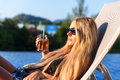 Young slim woman with glass of juice near swimming pool Royalty Free Stock Photo