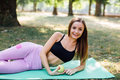 Young slim woman having snack after working out outdoors in the park. Sitting on the grass, eating juicy apple on fresh air Royalty Free Stock Photo