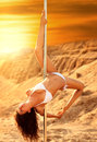 Young slim woman pole dance on sand background Royalty Free Stock Images