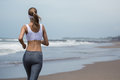 Young slim woman running on the beach. Back view. Royalty Free Stock Photo