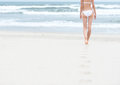 Young slim woman white swimsuit walking to sea ocean leaving footprints soft sand blue ocean waves foam background bathing Royalty Free Stock Photos