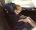 Young small boy sleeping in a child car seat tired and the back of Stock Image