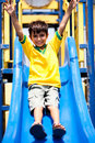 Young smart kid sliding down the swing Royalty Free Stock Photography