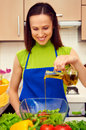 Young smiley housewife preparing vegetable salad Royalty Free Stock Photography