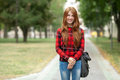 Young smiling adorable redhead student woman in red plaid jacket with folded hands posing outdoors on park path with blurred green Royalty Free Stock Photo