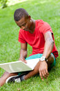 Young smiling african student sitting in grass with notebook outdoor summer man Royalty Free Stock Photos