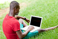 Young smiling african student sitting in grass with notebook outdoor summer man Royalty Free Stock Photo