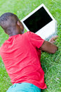 Young smiling african student sitting in grass with notebook outdoor summer man Stock Photography