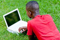 Young smiling african student sitting in grass with notebook outdoor summer man Royalty Free Stock Photography
