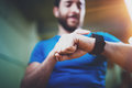 Young smiling athlete checking burned calories on electronic smart watch application after good indoor workout session Royalty Free Stock Photo
