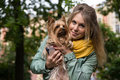 Young smiling blonde woman in city park small yorkshire terrier is on her hands pretty Royalty Free Stock Image