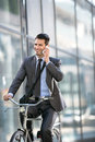 Young smiling business man with phone riding a bicycle Royalty Free Stock Photo