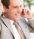 Young smiling business man using cell phone with h Stock Images