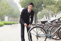 Young smiling businessman locking up his bicycle on a city street in beijing looking at camera Stock Image