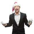 Young smiling businessman in santa hat holding money Royalty Free Stock Photo