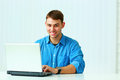 Young smiling businessman typing on the laptop and looking at camera in office Royalty Free Stock Image
